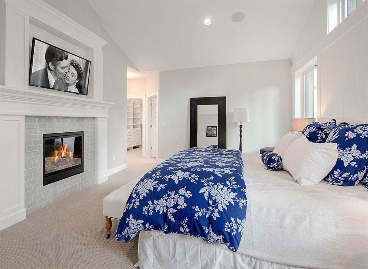 There's a brick fireplace in front of the bed topped with a wide-screen TV.