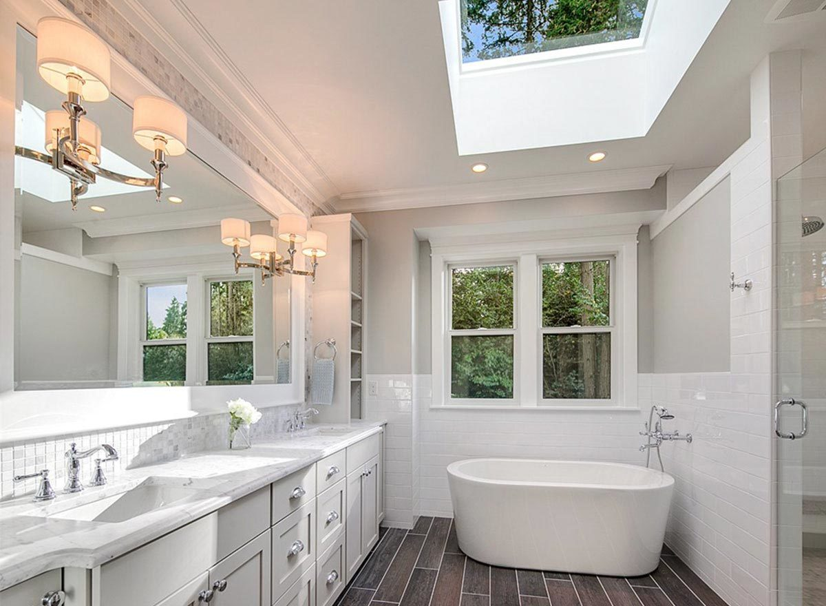 The primary bathroom is equipped with a dual sink vanity, a walk-in shower, and a freestanding tub.