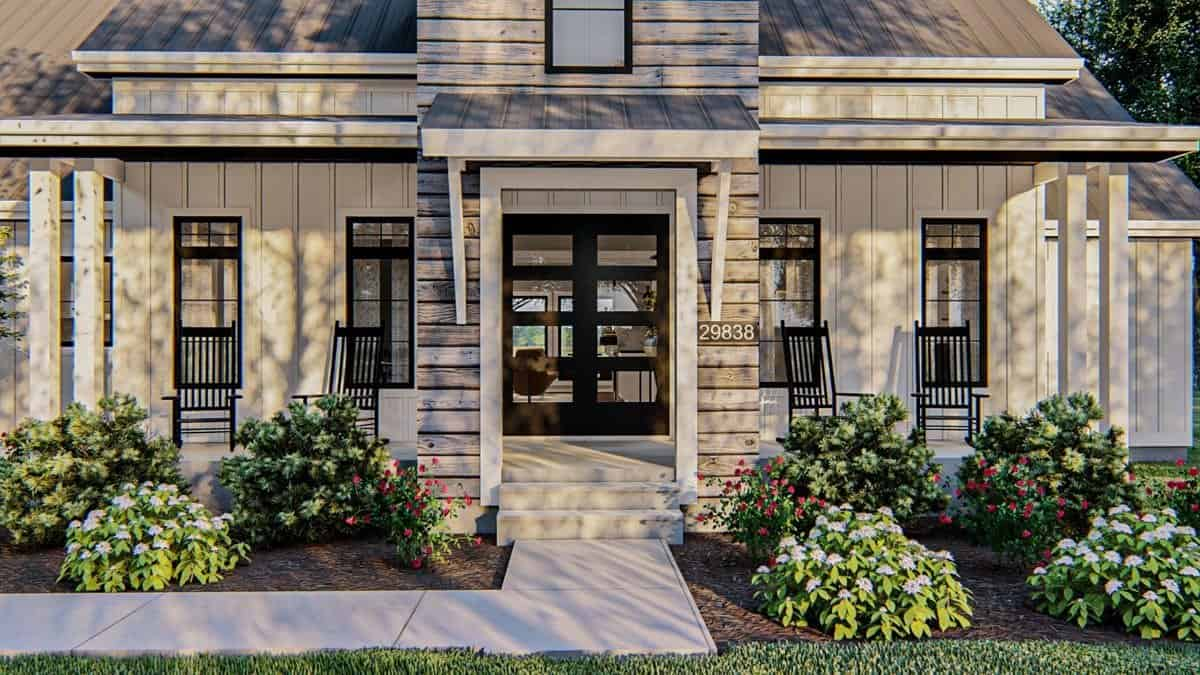 Home entry with a covered porch filled with black rocking chairs and a french front door.