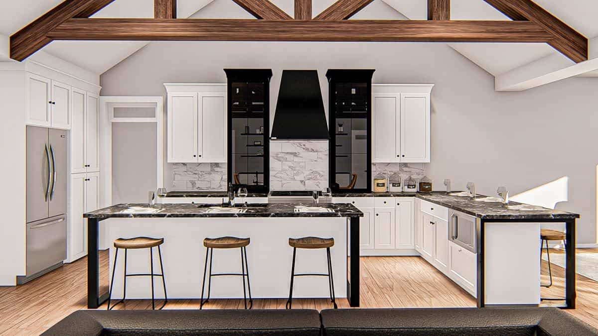 Kitchen with white cabinetry, black marble countertops, slate appliances, and a breakfast island.