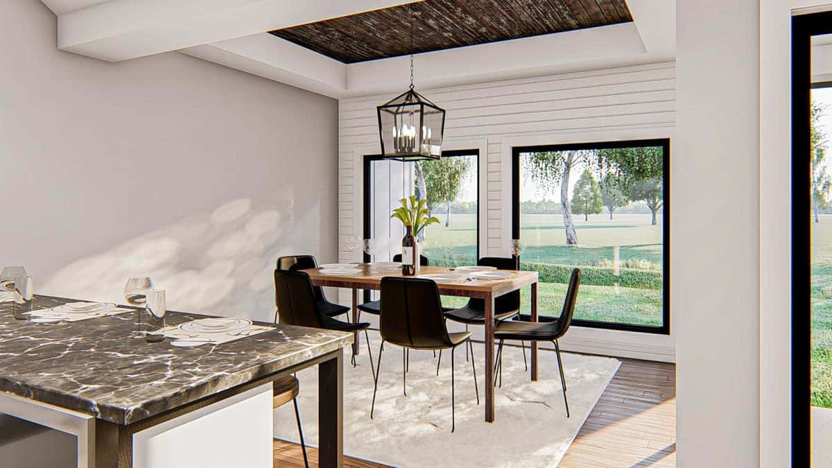 Breakfast nook with black modern chairs, a beige area rug, a wooden dining table, and a lantern pendant hanging from the tray ceiling.