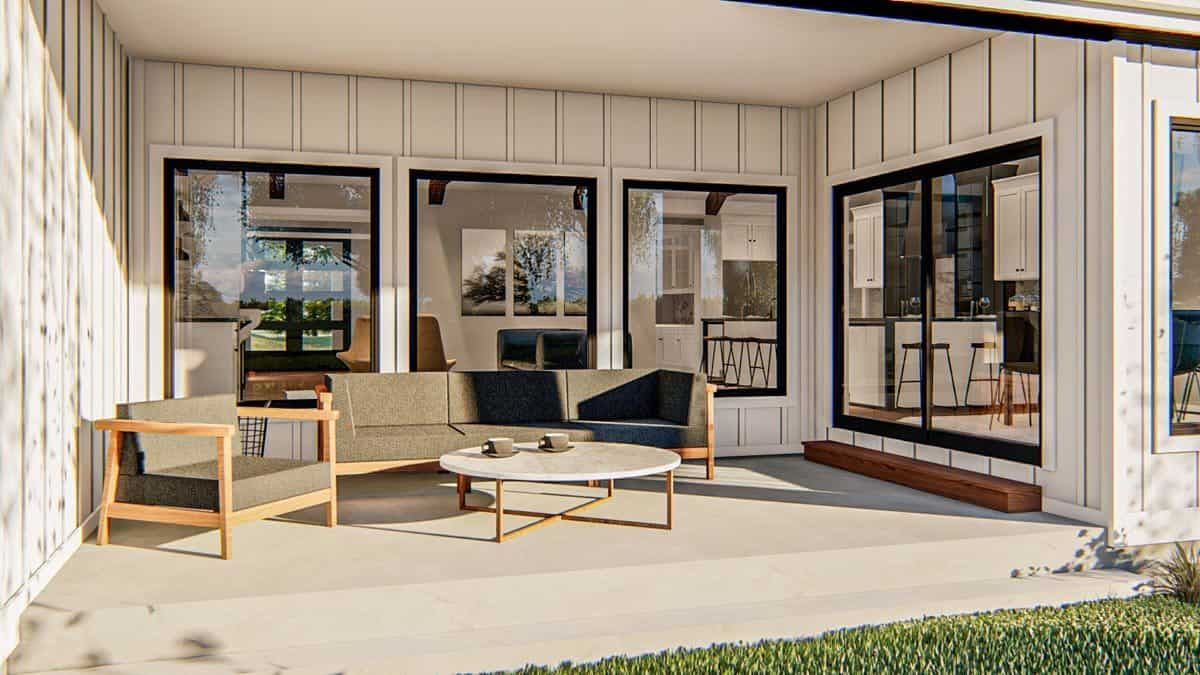 Covered patio with cushioned seats and a round coffee table over concrete flooring.