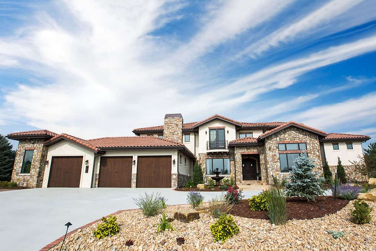 Front exterior view showing the white stucco siding, decorative stone accents, and clay terracotta tile roofs.