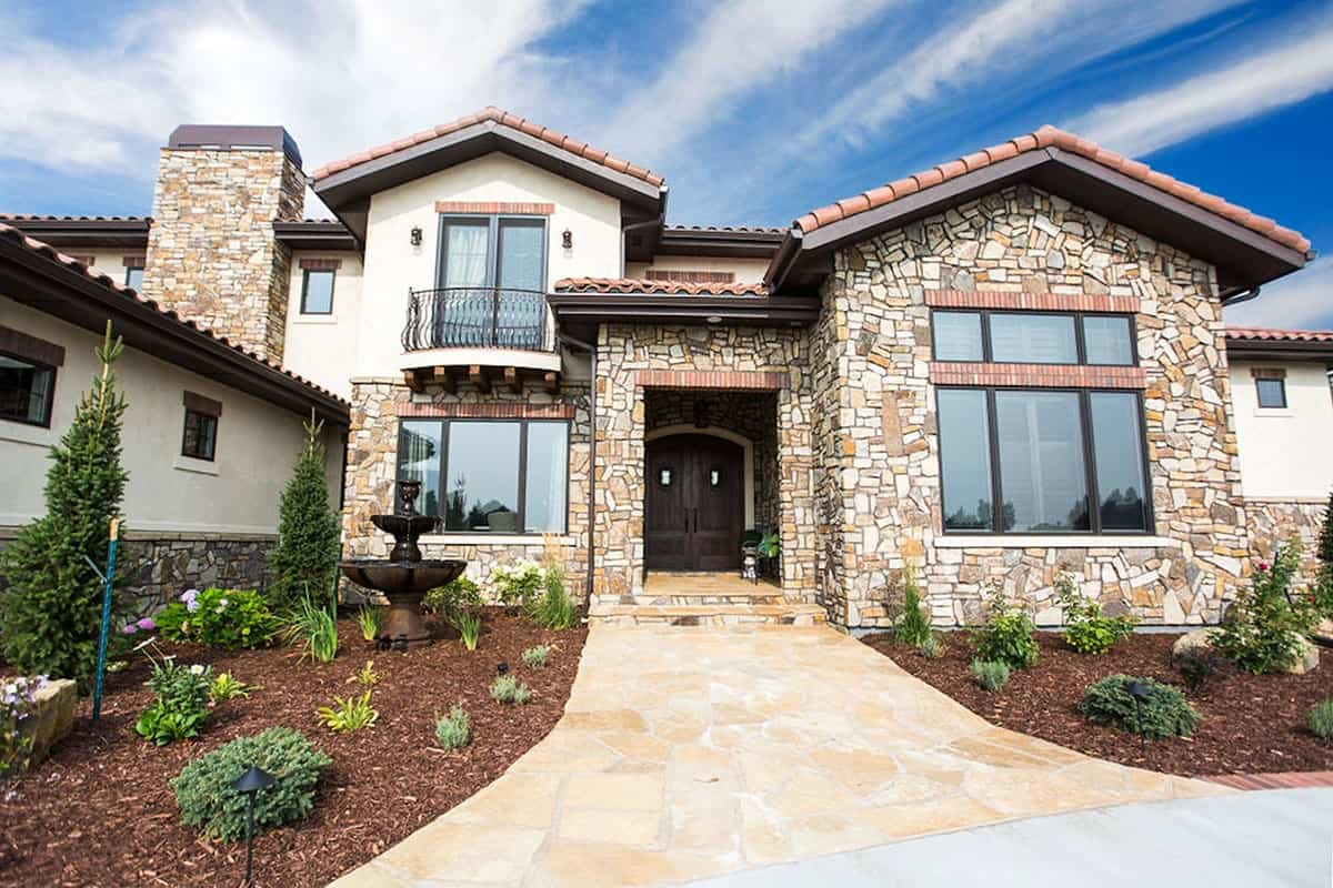 A flagstone walkway leads to the covered entry with an arched double door.