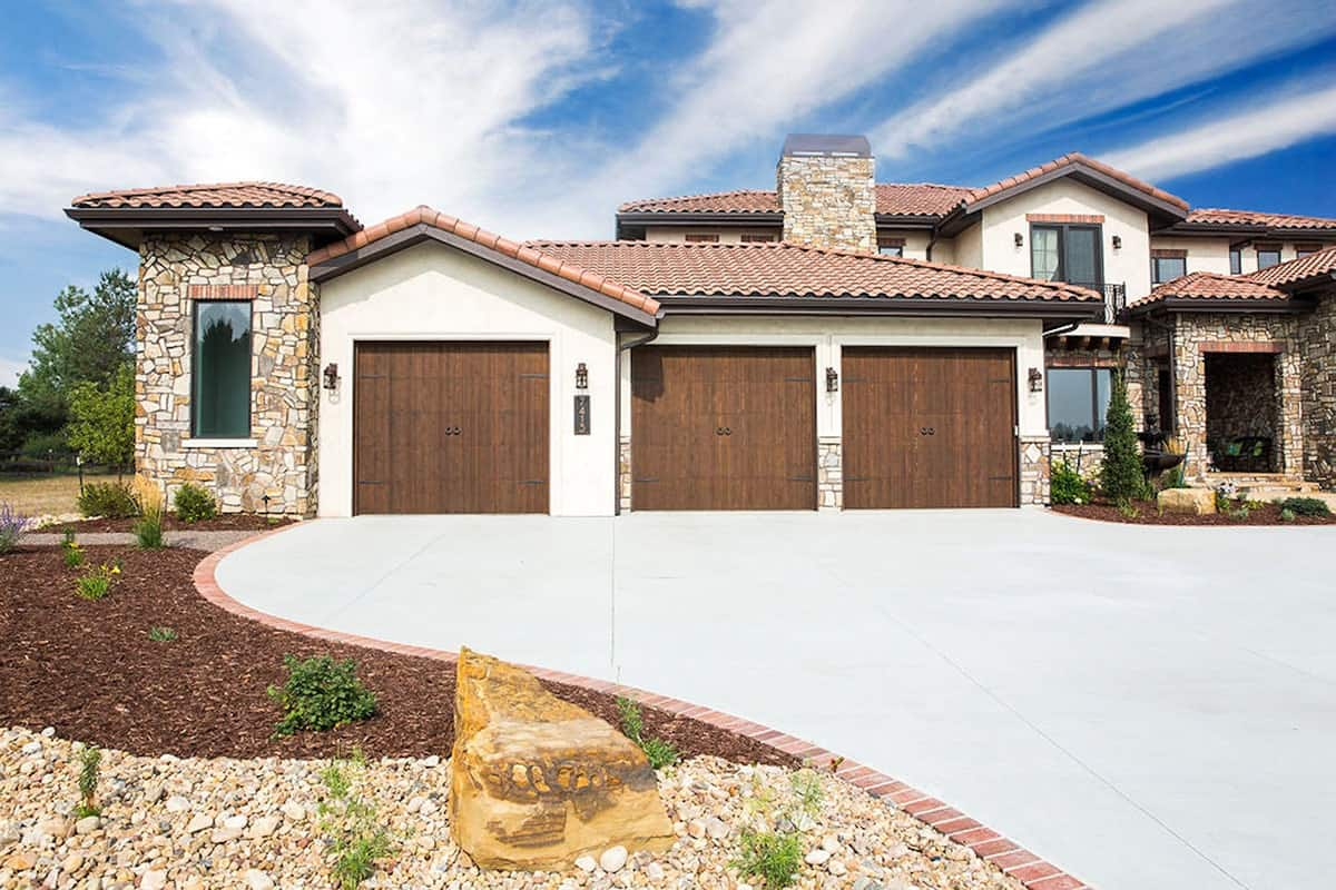 The concrete tiled driveway complements the oversized three-car garage.