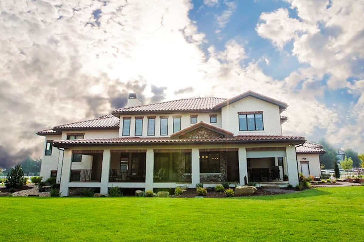 Rear exterior view showing the covered veranda and a lush lawn surrounding the house.