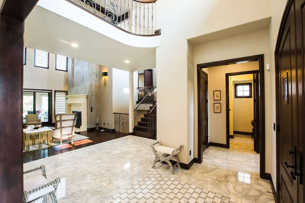 Foyer with wooden double door, marble tile flooring, and cushioned seats.
