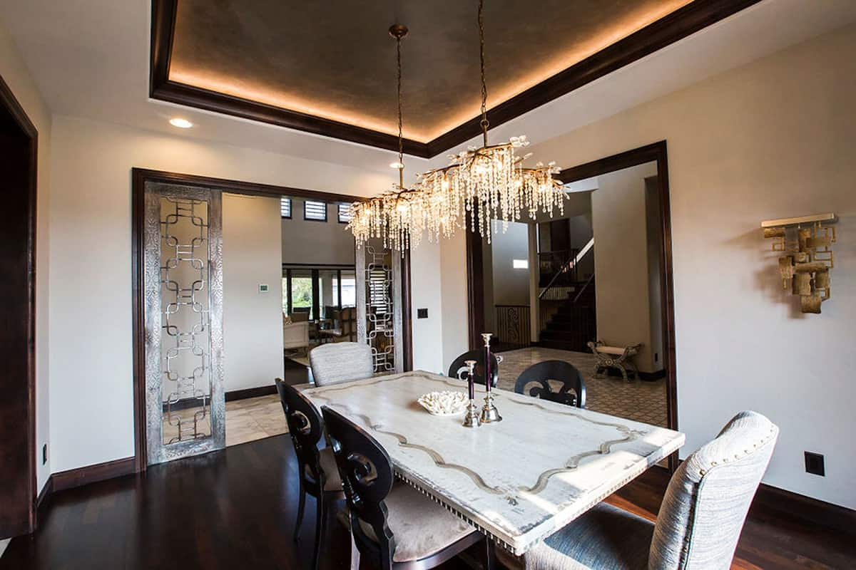 The dining room offers a rectangular dining table, cozy seats, and beaded pendants hanging from the illuminating tray ceiling.