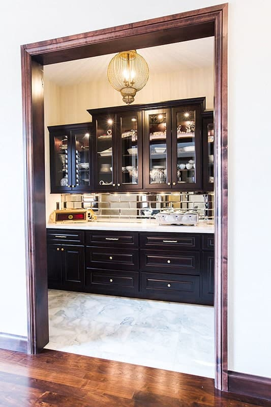 Butlery with glass front and dark wood cabinets, marble countertops, and mirrored subway tile backsplash.