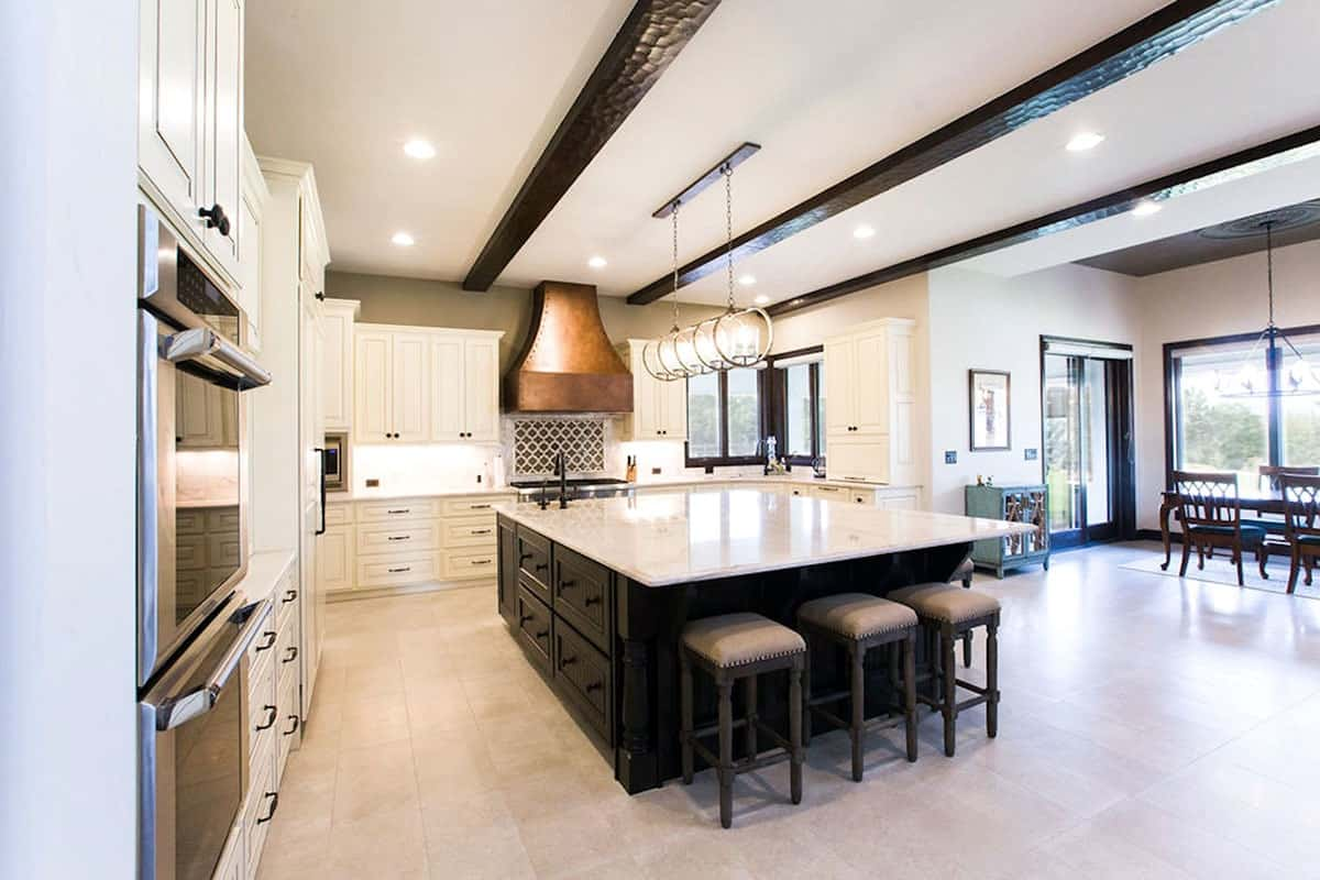 The kitchen is equipped with stainless steel appliances, white cabinetry, and an immense island illuminated by round pendants.