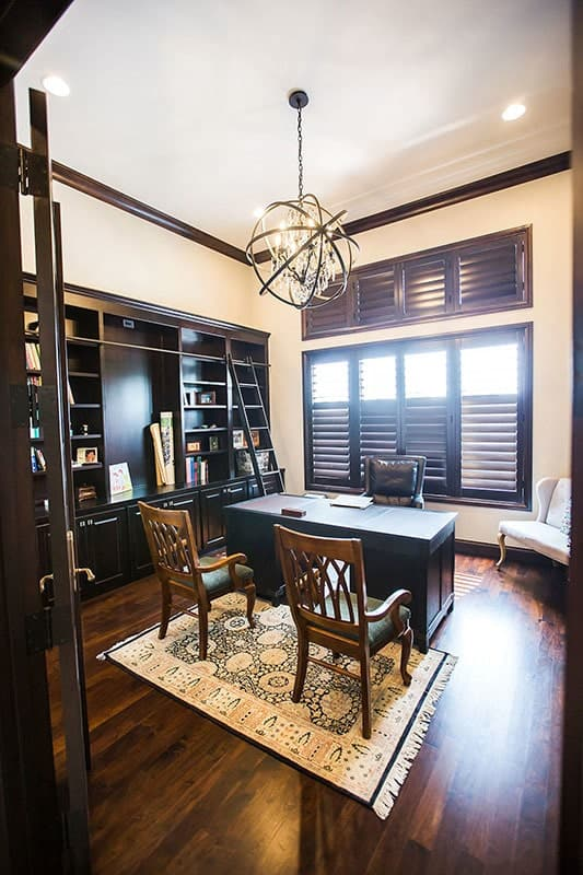 Study with dark wood desk, cushioned seats, a spherical pendant light, and a built-in bookcase.
