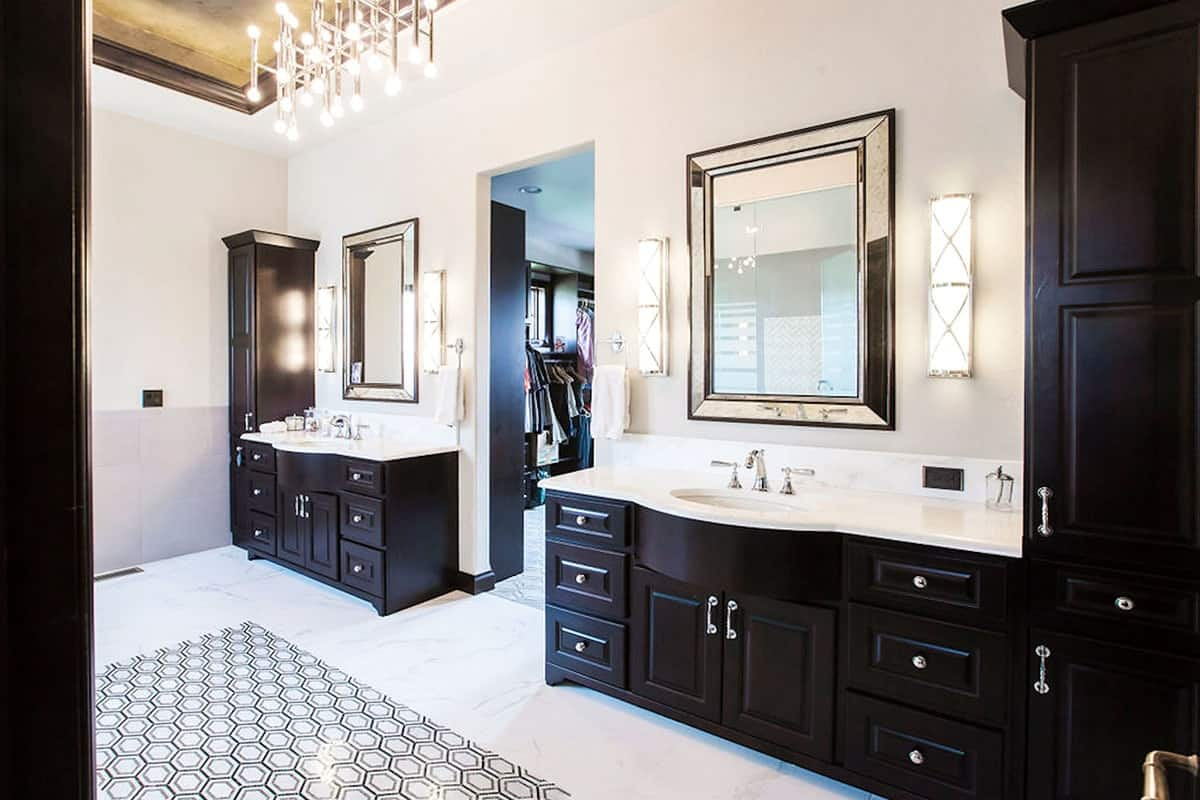 The primary bathroom features two vanities with white marble countertops, chrome-framed mirrors, and cylindrical sconces.The primary bathroom features two vanities with white marble countertops, chrome-framed mirrors, and cylindrical sconces.
