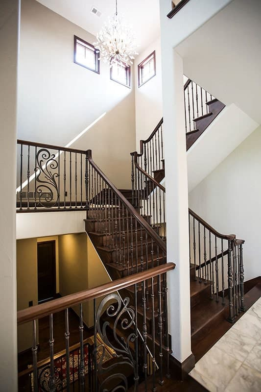 A crystal chandelier along with small wooden framed windows brighten the ornate staircase.