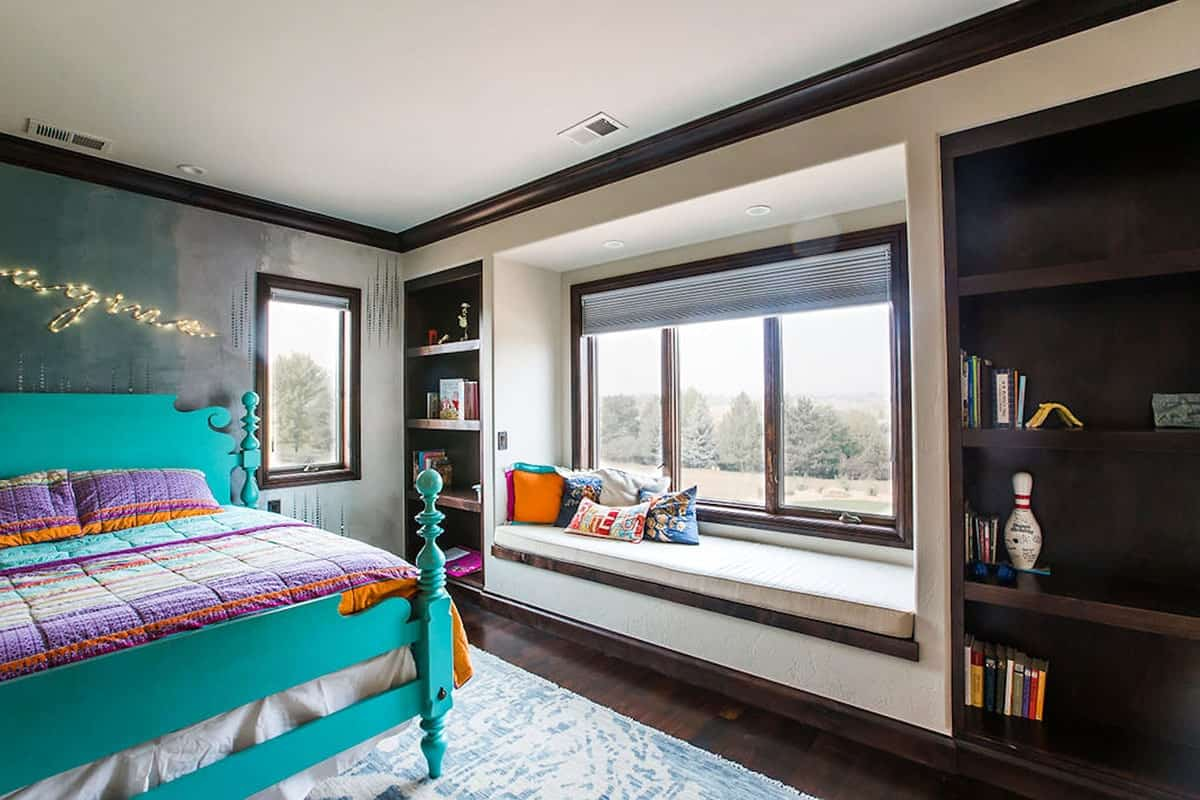 This bedroom has a green bed, inset shelves, and a window seat.