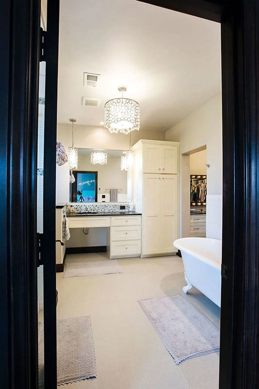 Bathroom with a clawfoot tub and white vanity attached to a full-length cabinet.