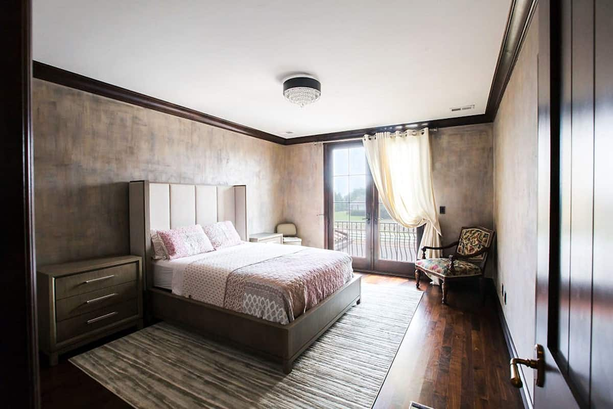 Another bedroom with a wingback bed, a patterned armchair, and a private balcony.