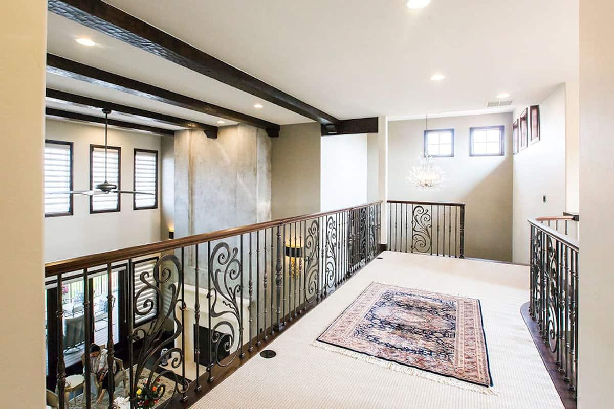 Balcony bridge with a tasseled rug and ornate railings overlooking the living room below.