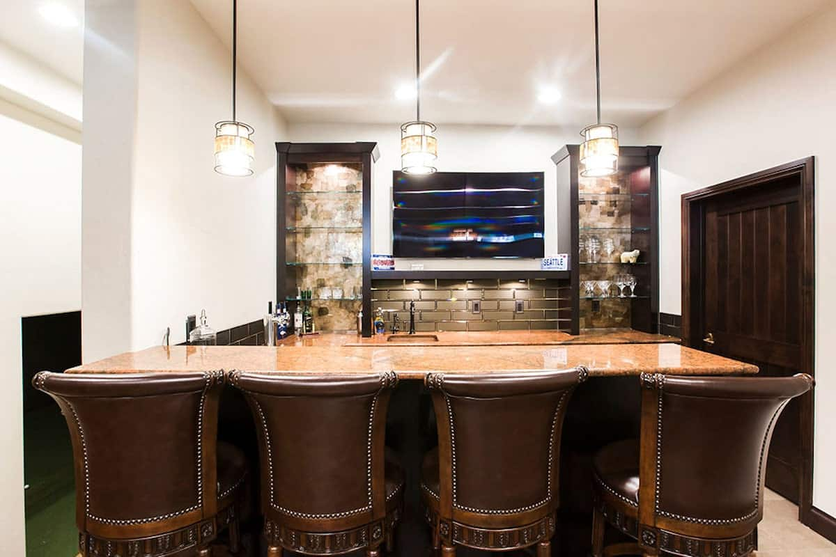 Wet bar with glass shelvings, granite countertops, glass pendants, and leather counter chairs.