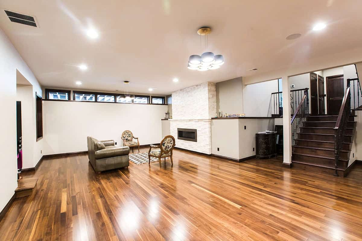 Spacious recreation room with hardwood flooring and a regular white ceiling.