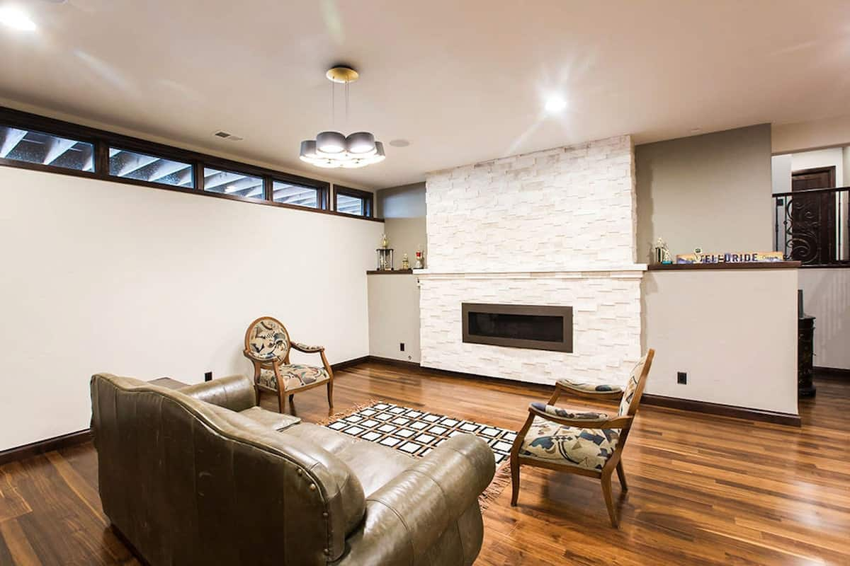 A closer look shows the cluster chandelier, a modern fireplace, leather sofa, and round back chairs.