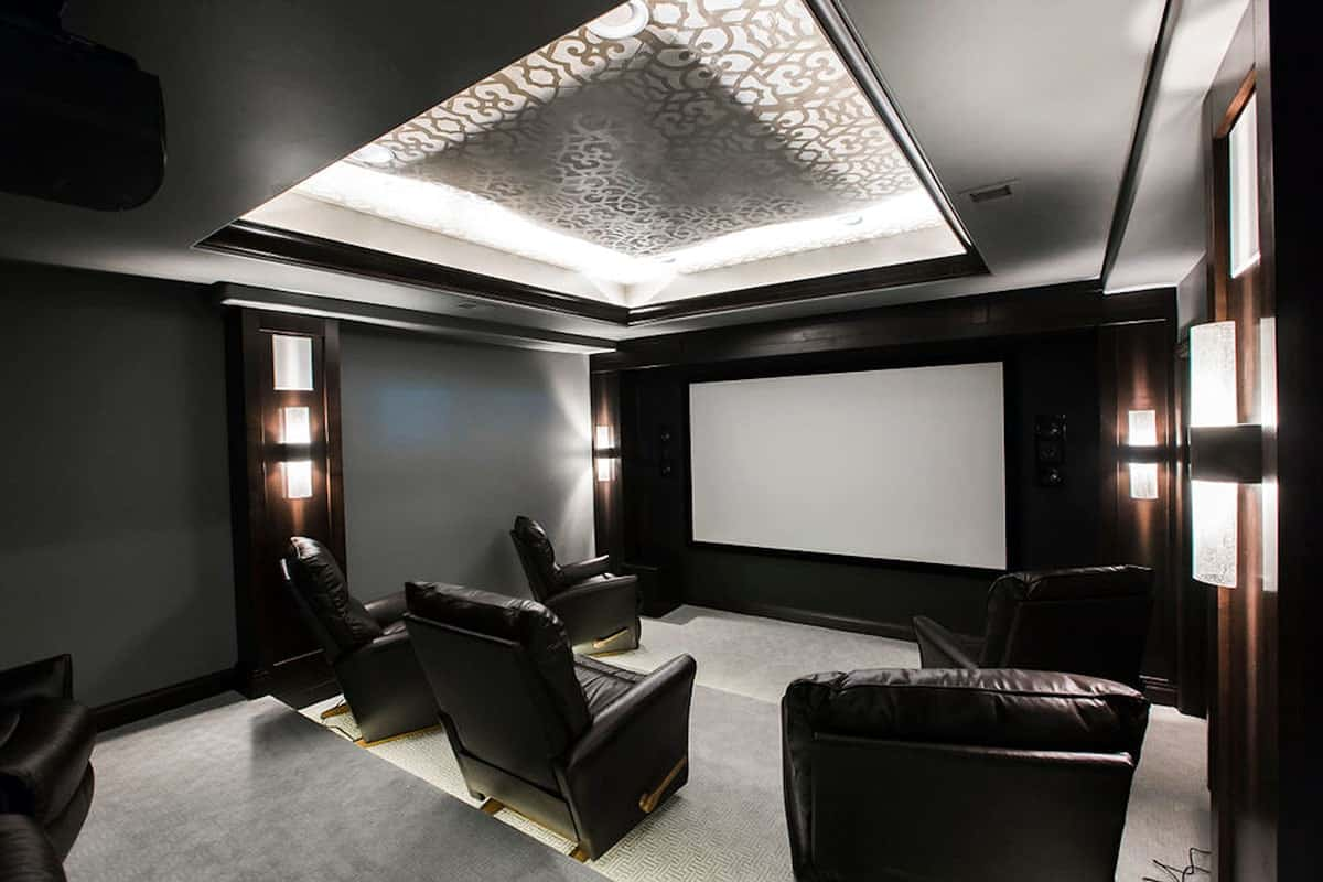 Home theater with a decorative tray ceiling, cylindrical sconces, and black leather recliners.