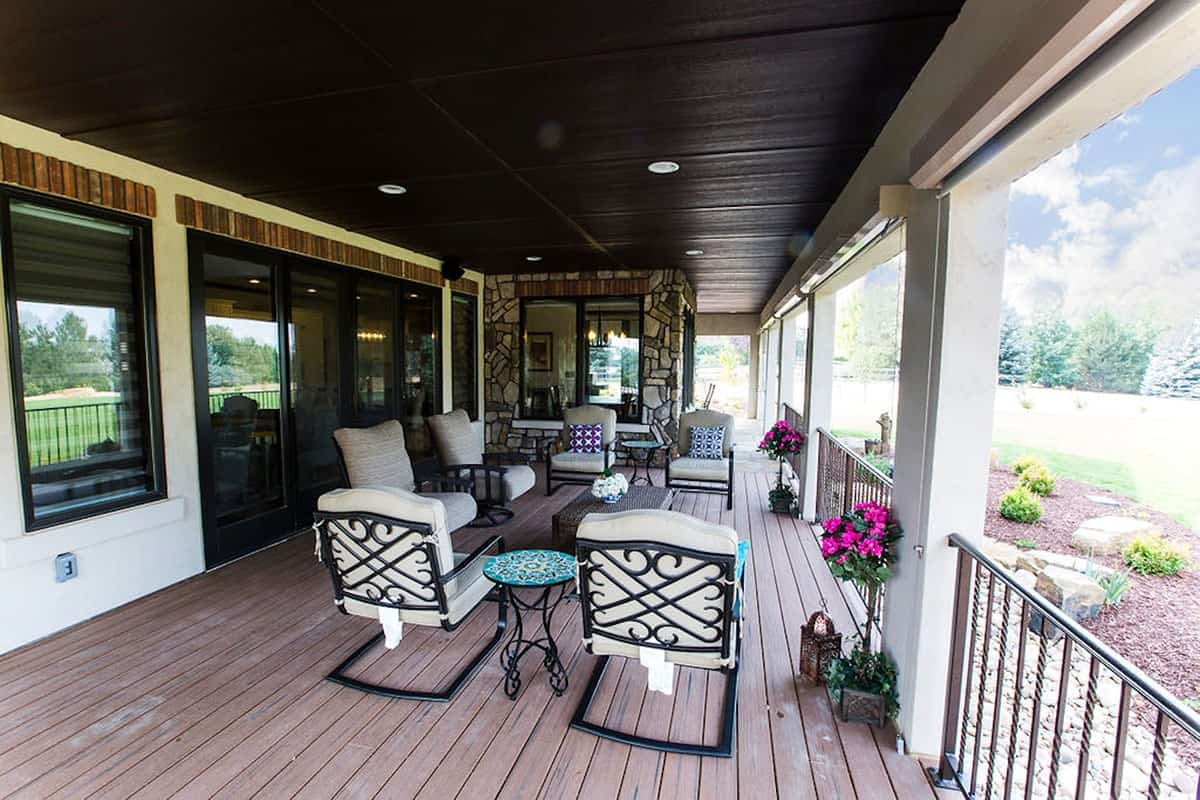 The covered veranda is filled with cushioned metal chairs and a wicker coffee table over wide plank flooring.