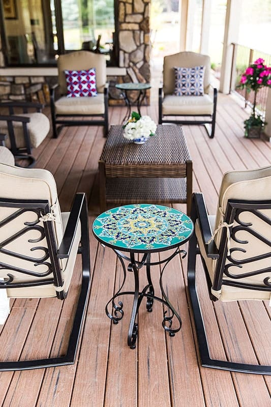 Cushioned metal chairs along with round side tables surround the wicker center table.