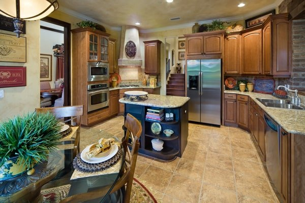 Eat-in kitchen with wooden cabinetry, granite countertops, a double bowl sink, and a small center island.