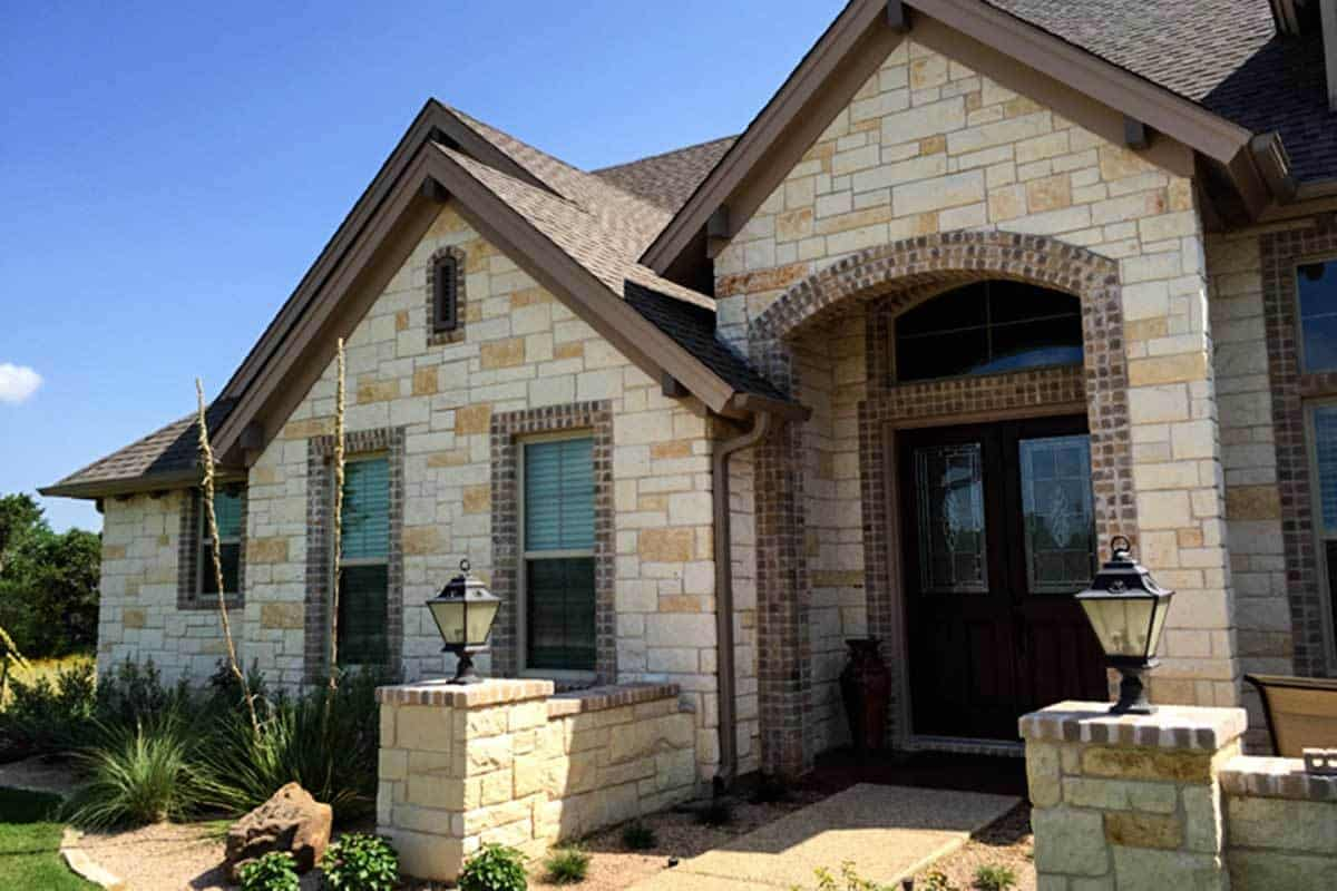 Home entry with a brick archway and a french front door.