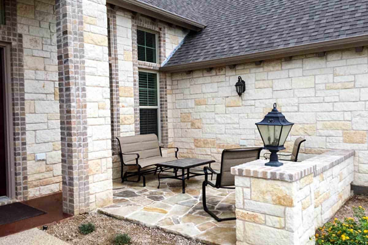 The courtyard is filled with metal seats and a matching table over flagstone flooring.