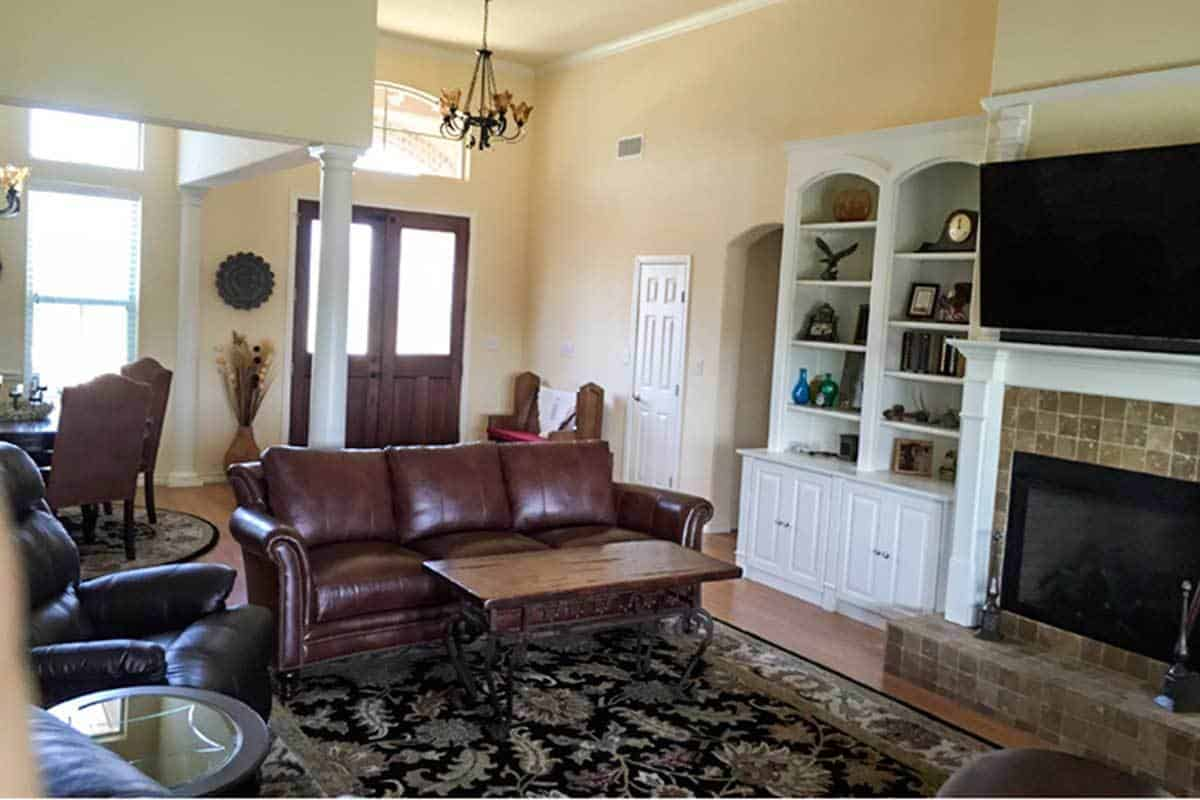Behind the leather sectional is the foyer with a french entry door, arched transom, and a wrought iron chandelier.