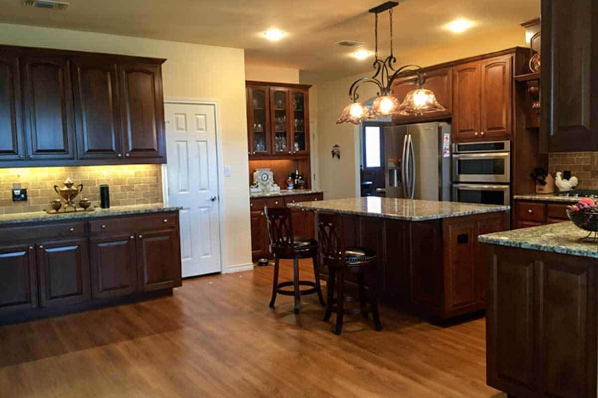 The kitchen is equipped with granite countertops, stainless steel appliances, brick backsplash, dark wood cabinetry, and a breakfast island.