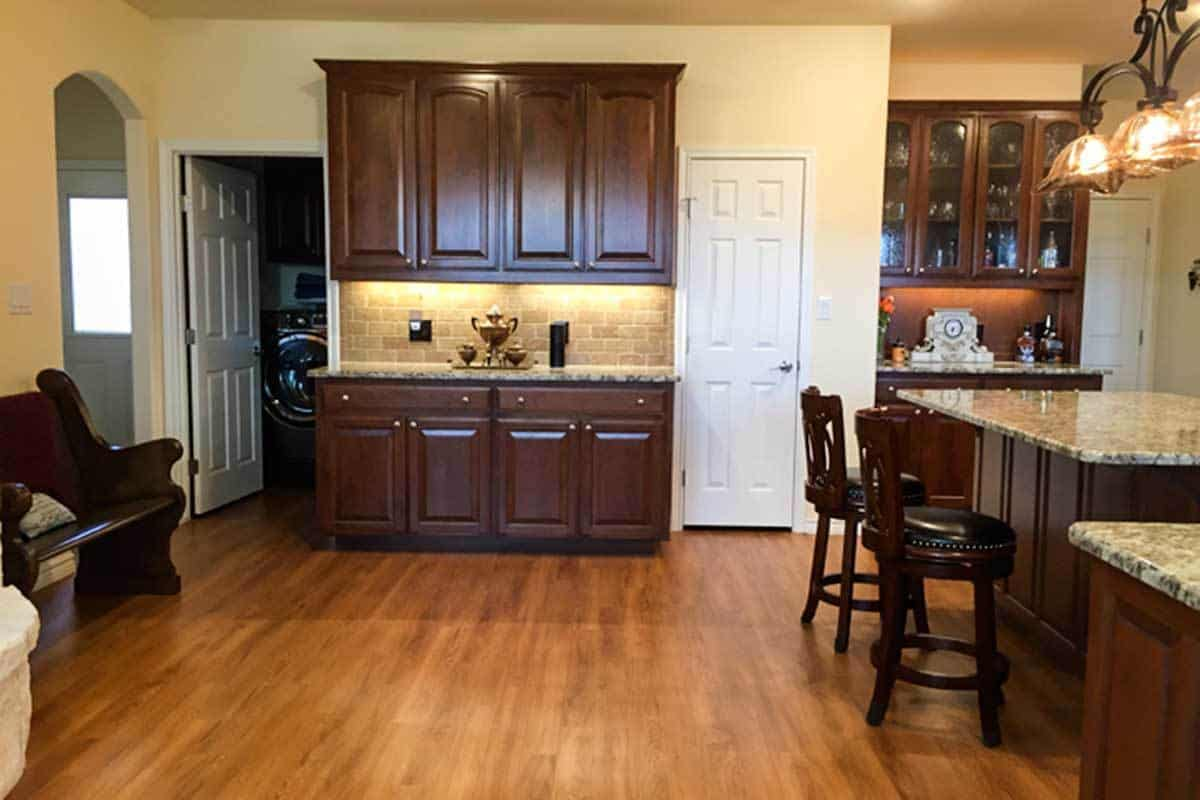 White doors leading to the laundry area and pantry flank the granite top bar.