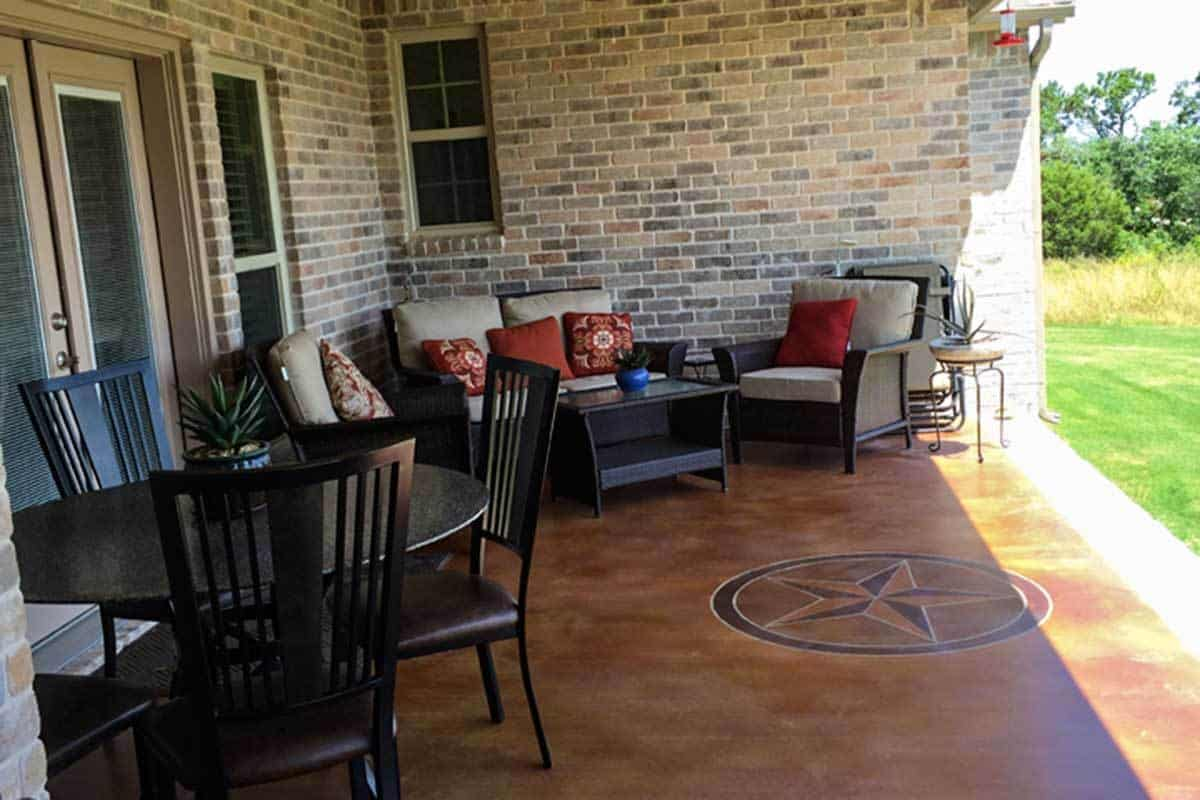 The outdoor living offers a wooden coffee table and cushioned seats accented with red pillows.