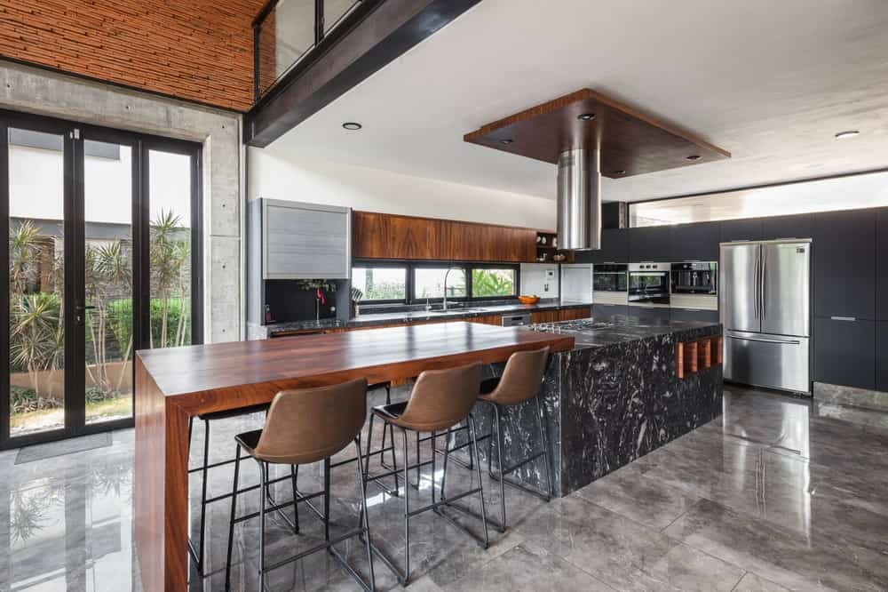 This is a close look at the kitchen with a alrge kicthen island that has an attached wooden table to its black marble island.