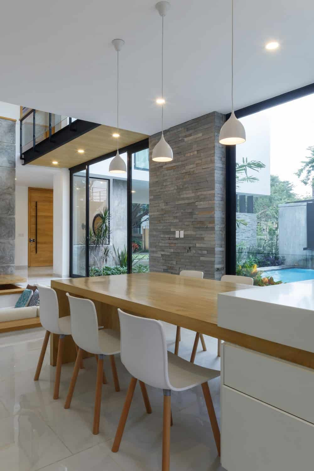The wooden dining table is surrounded by white modern chairs and topped with a row of white modern pendant lights.