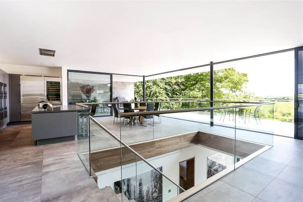 This is a close look at the indoor balcony and staircase of the house with glass railings to pair with the surrounding glass walls of the house.