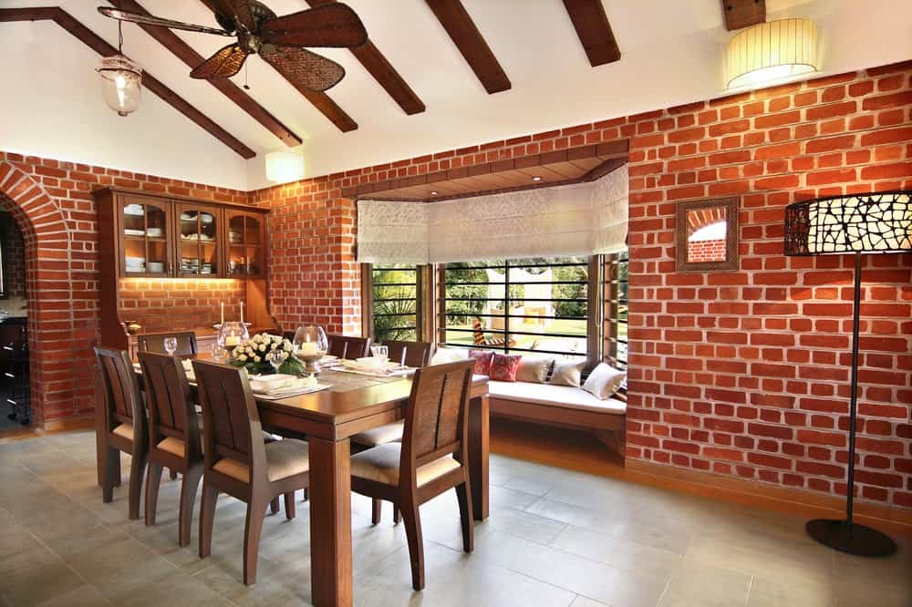 The dining room has a wooden dining set that pairs well with the surrounding red brick walls with a reading nook under the large window.