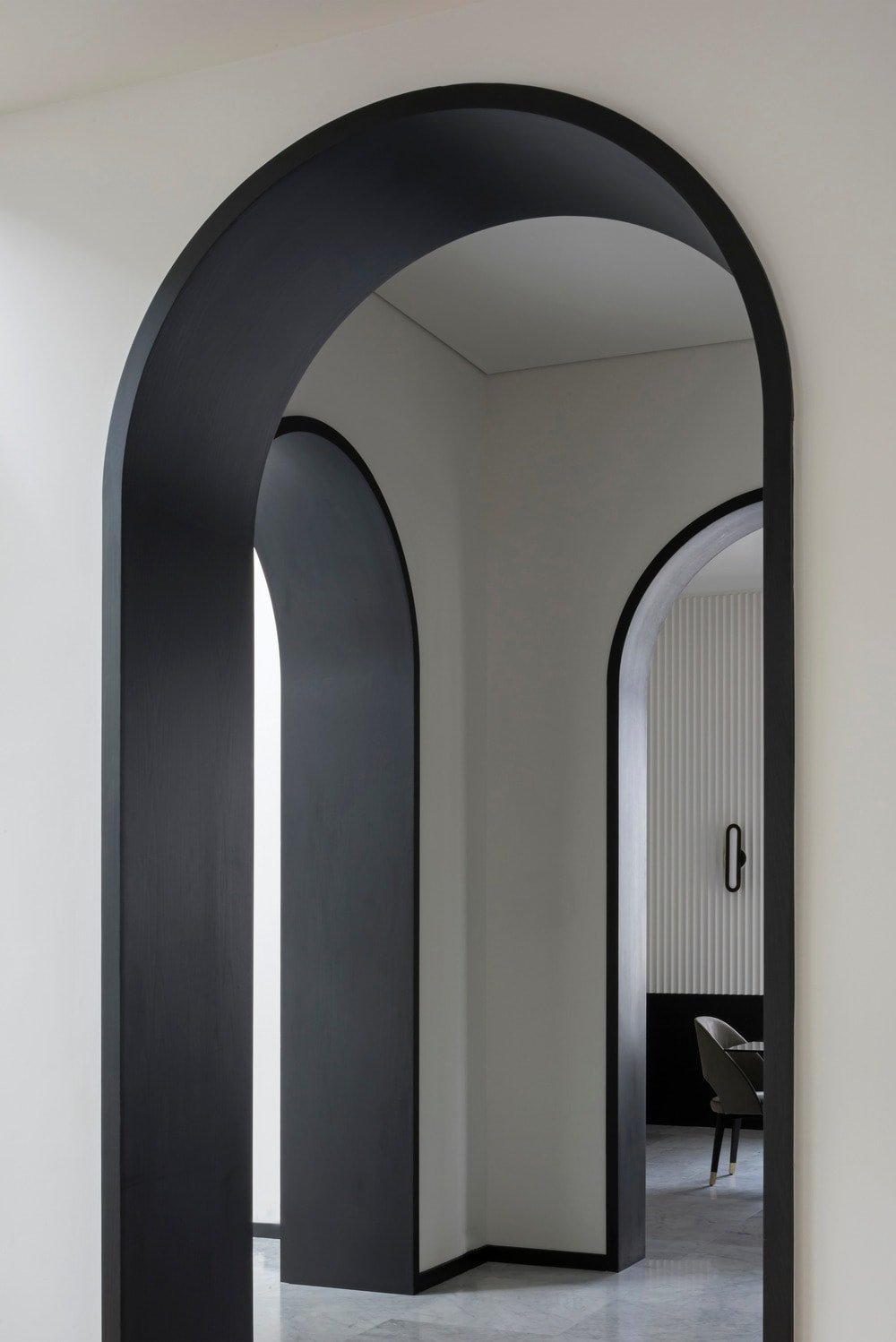 This is a look at the arched entryways of the house that has black tones on the inside to contrast the white walls and ceiling.