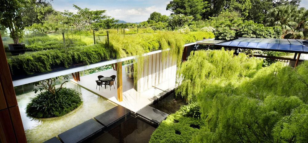 This is a look at the ground floor from the vantage of the second-floor balcony that is has its own lush landscaping of shrubs that seem to waterfall below.