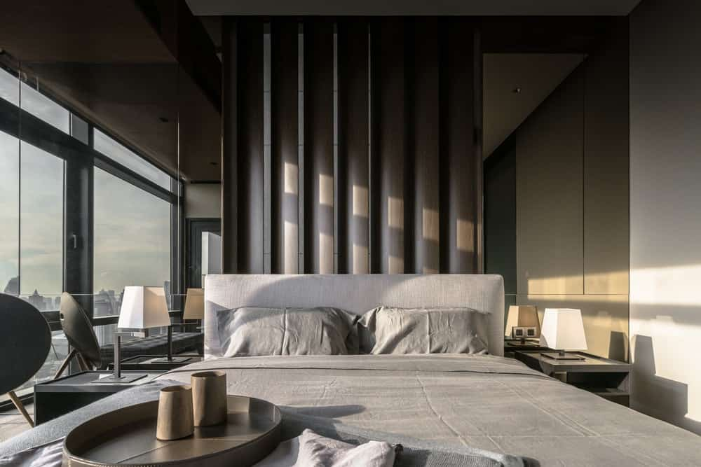 The bedroom has a gray bed with a cushioned headboard adorned by the patterned panel behind the headboard.