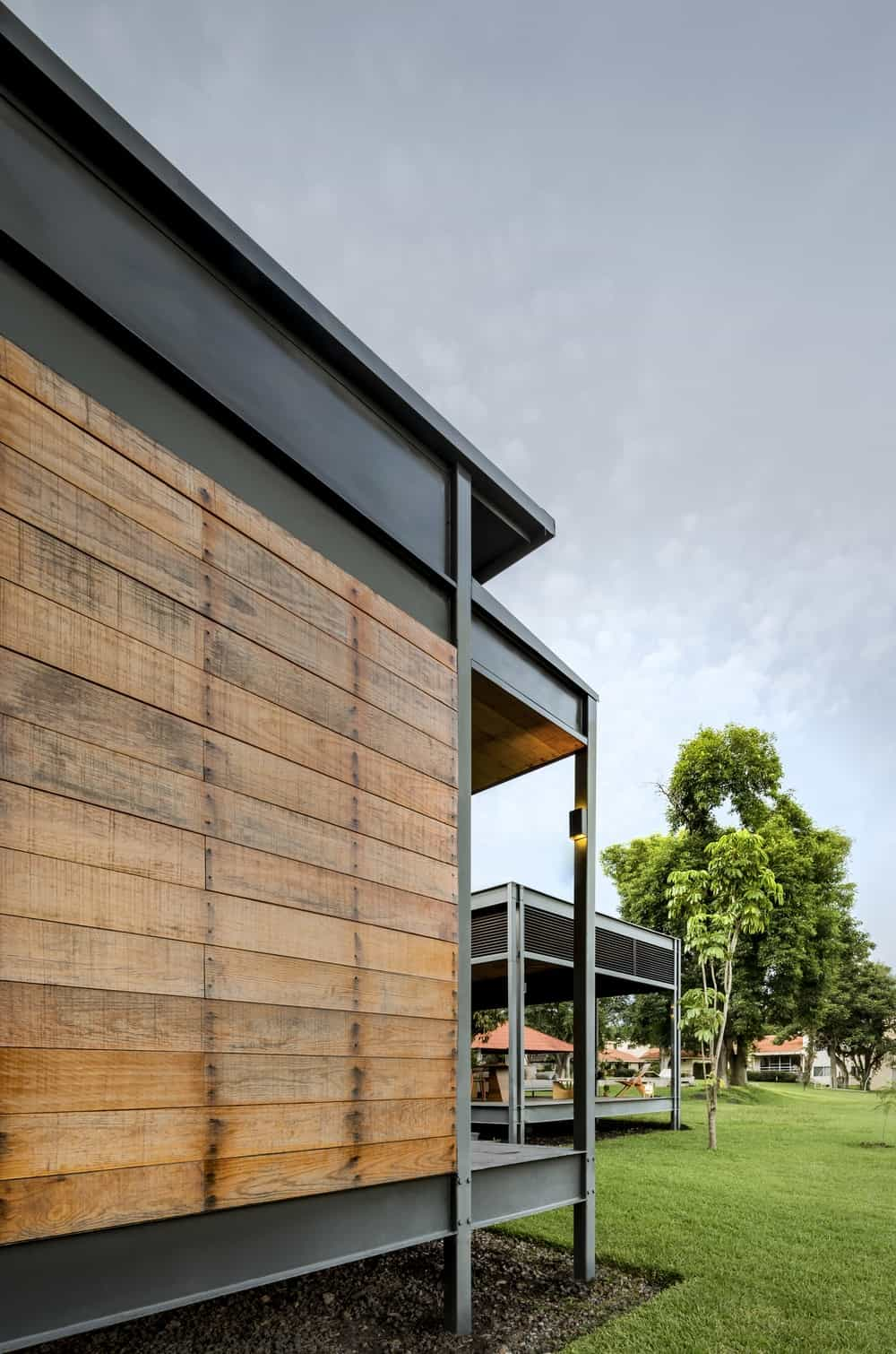 This side of the house shows the wooden exterior walls that give an earthy aesthetic to the cold gray steel beams of the exterior.