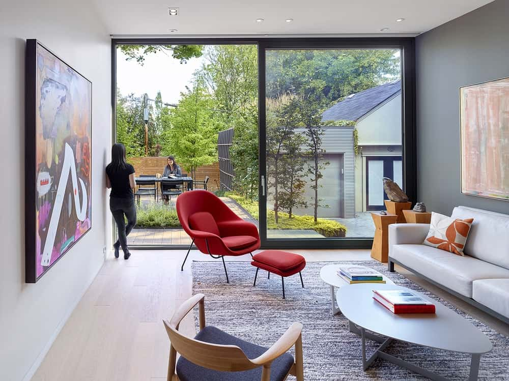 This is the bright living room with a large sliding glass wall on the far side illuminating the sofa set across from the large colorful painting.