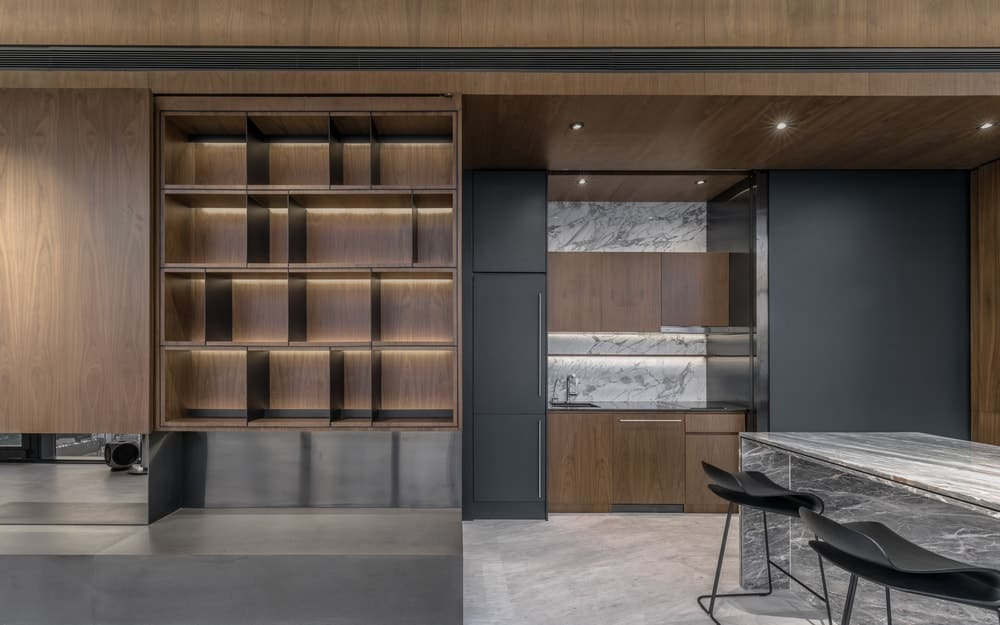 On the side of this wooden shelving is the large structures of the kitchen with black and wooden elements.
