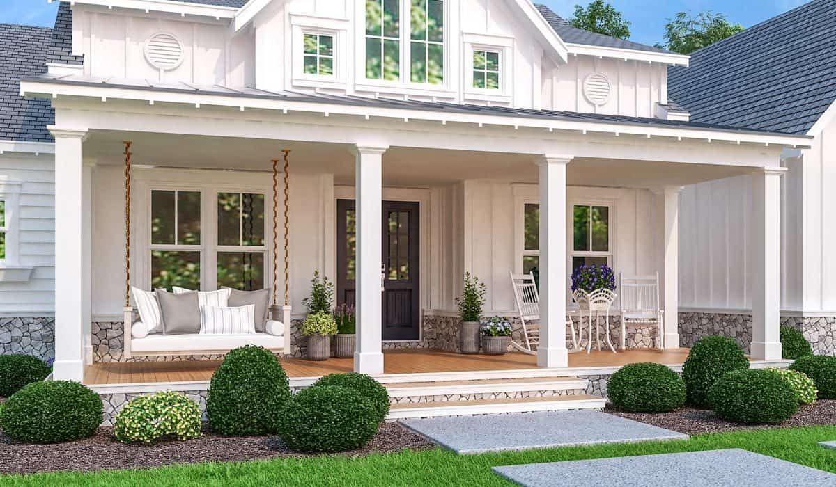 The covered front porch is filled with white rocking chairs, fresh potted plants, and a swinging bench filled with gray and striped pillows.