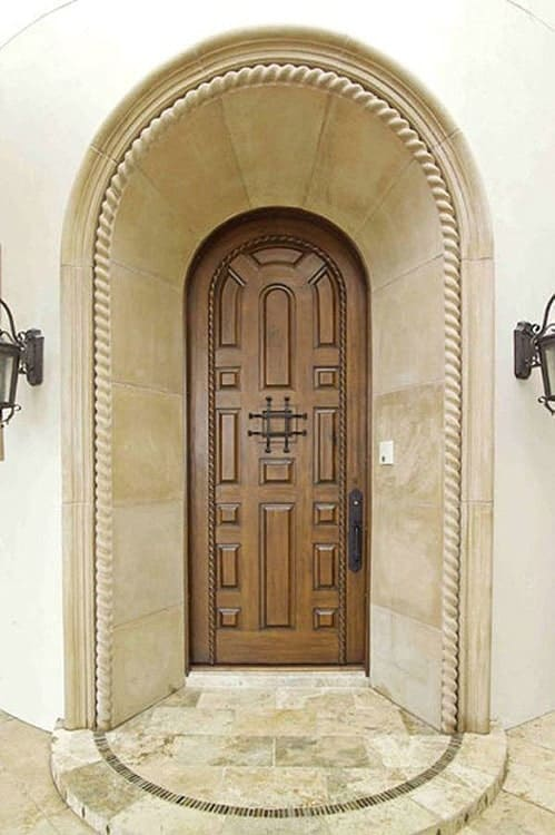 Arched entry with a wooden front door flanked by wrought iron sconces.