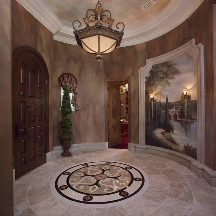 Circular gallery foyer with an oversized pendant, a wall mural, and limestone flooring adorned with a round decal.