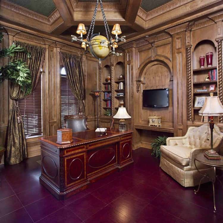 The study has cozy seats, a wooden desk, arched insets, and louvered windows dressed in dark draperies.