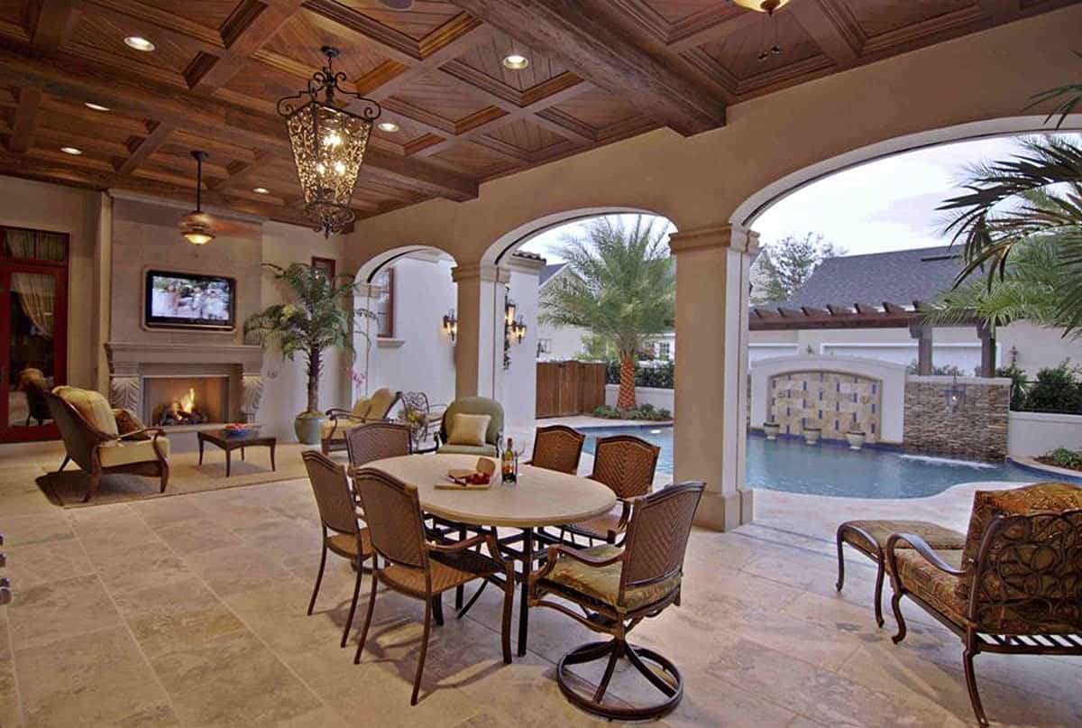 Covered patio with outdoor living and dining topped with wooden coffered ceiling.