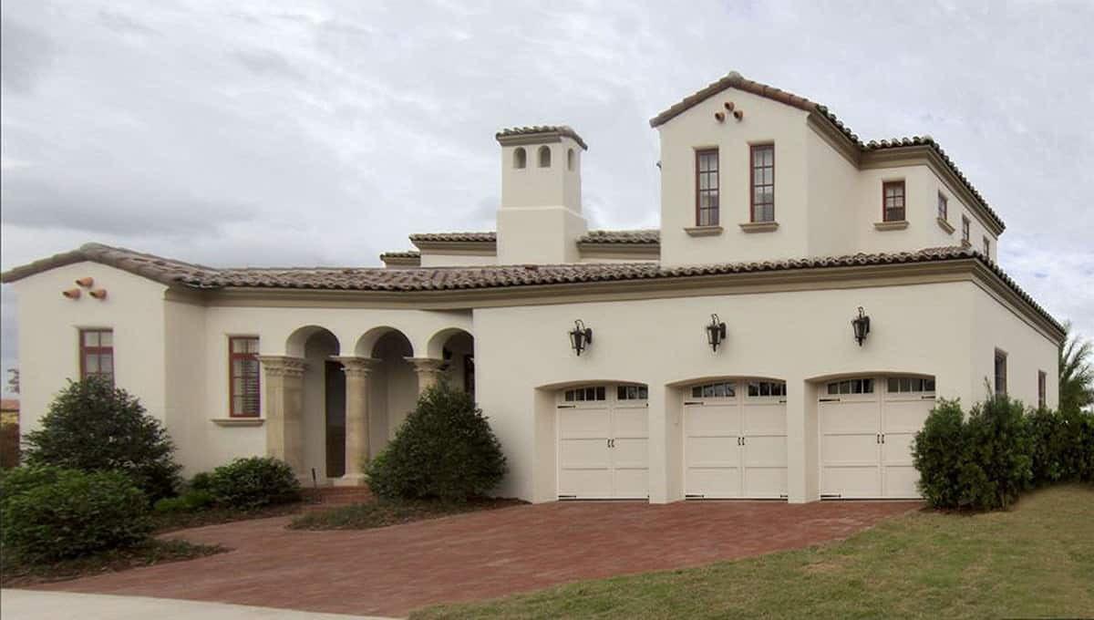 Side exterior view showing the loggia and three-car garage topped with outdoor sconces.